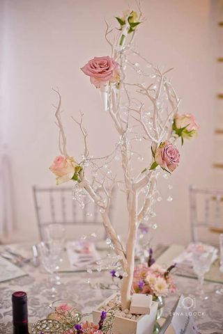 white tree with crystal fairy lights and fresh roses in test tubes